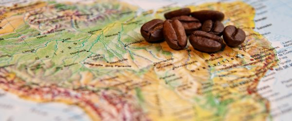 Where does coffee originate, and who produces the most?